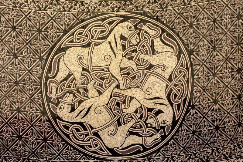Ornamento céltico de tres caballos en la tela Símbolo antiguo de imagen de archivo