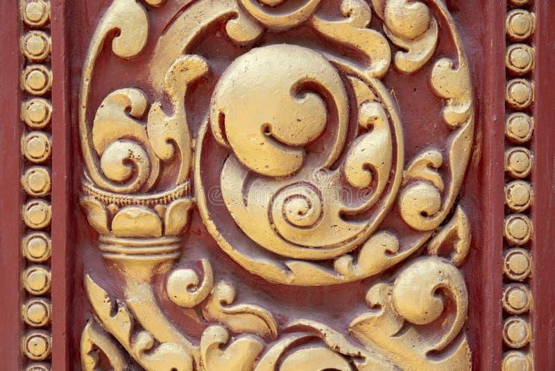Ornamento cinzelado de madeira pintado em vermelho e em dourado Cinzeladura de madeira do khmer tradicional Detalhe histórico do  fotografia de stock