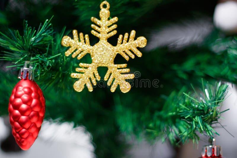 Ornamento de la Navidad con los copos de nieve del oro, el cono del pino rojo, la Feliz Navidad y la Feliz Año Nuevo fotos de archivo libres de regalías