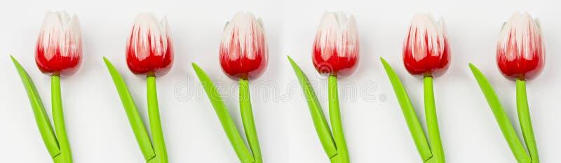 Ornamento de las flores artificiales, tulipanes rojos de madera en un fondo blanco Ornamento del estampado de plores foto de archivo