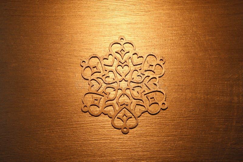 Ornamento de oro del copo de nieve en fondo de oro imágenes de archivo libres de regalías