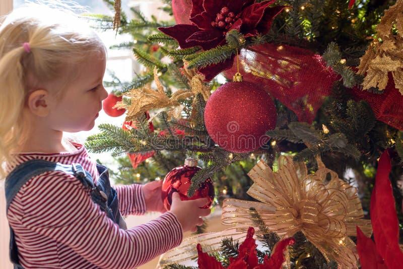 Ornamento de vidro tocante da árvore de Natal da moça foto de stock royalty free