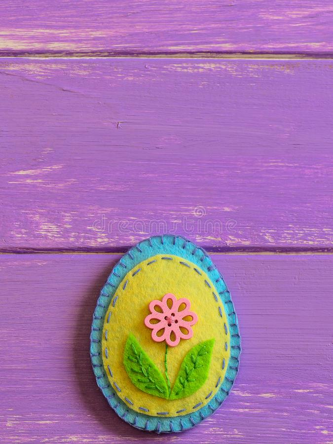 Ornamento decorativo del huevo de Pascua del fieltro en un fondo de madera con el espacio de la copia Artes de costura hechos a m foto de archivo