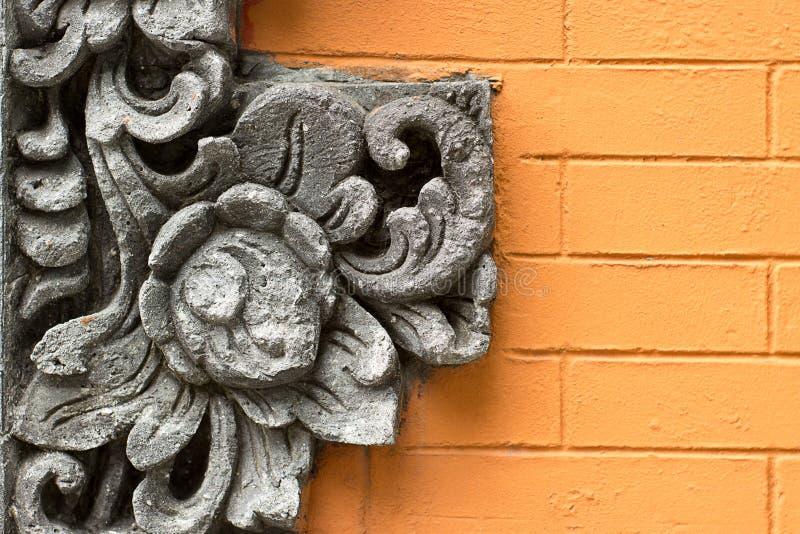 Ornamento della decorazione del fiore del cemento sul muro di mattoni arancio fotografie stock libere da diritti