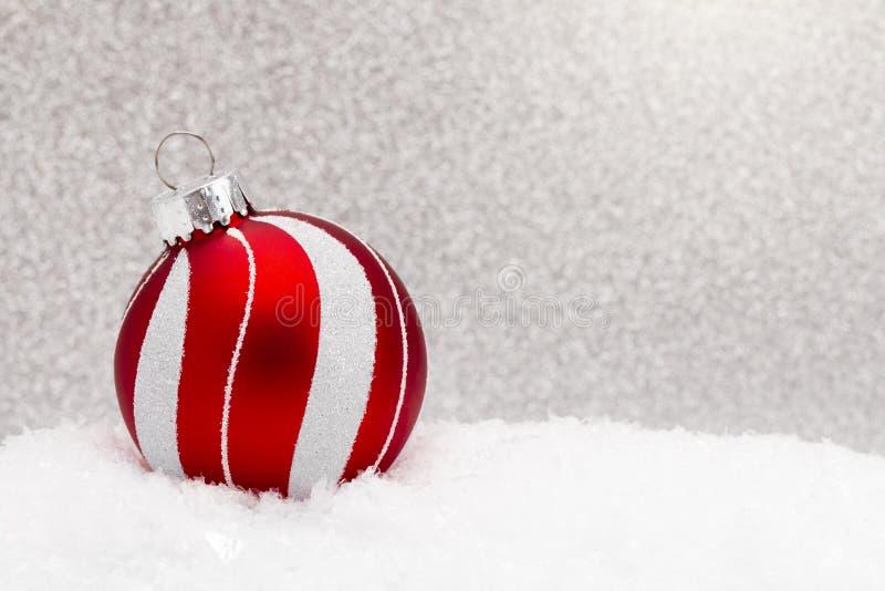 Ornamento di Natale nella neve con un fondo luccicante fotografia stock libera da diritti