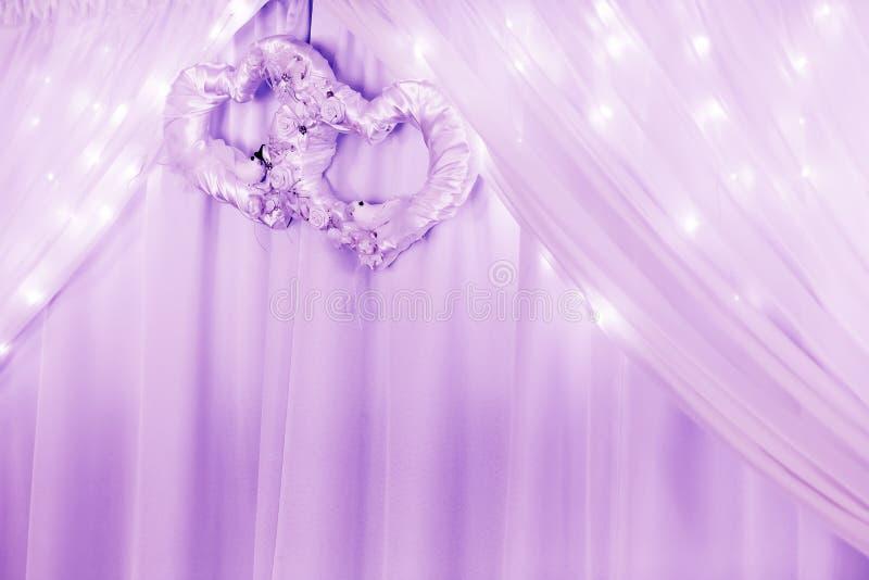 Ornamento di nozze con due cuori e tenda e luci fotografia stock libera da diritti