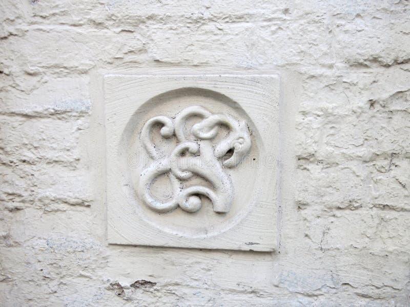 Ornamento di un poco drago su un muro di mattoni segnato bianco fotografia stock libera da diritti