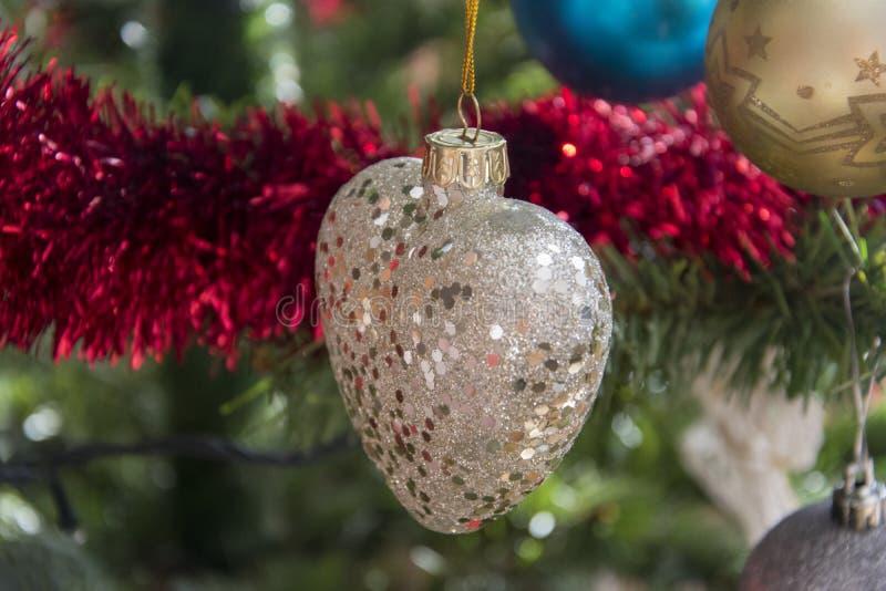 Ornamento do coração que pendura na árvore de Natal Fim bonito acima do HOL imagem de stock