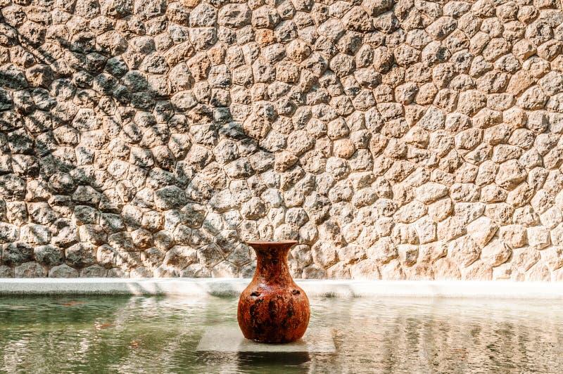 Ornamento do jardim da urna ou do vaso do vintage na lagoa e na parede de pedra fotografia de stock