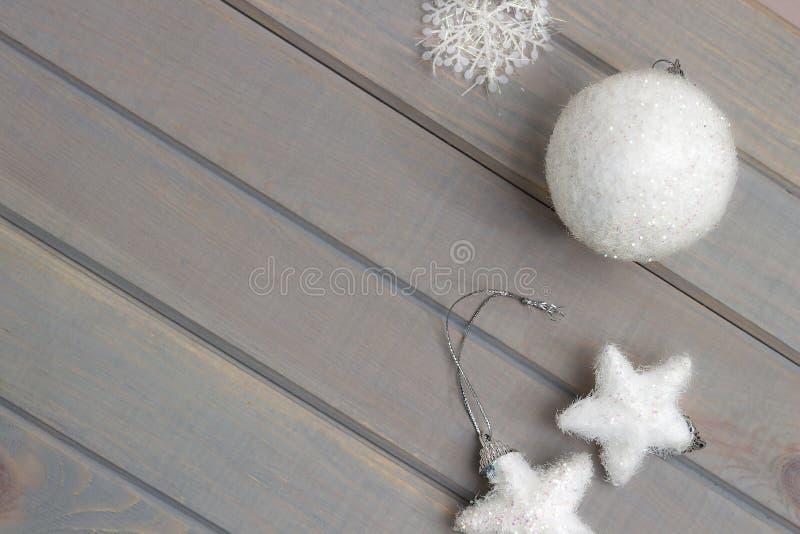 Ornamento do Natal no branco em uma luz - fundo de madeira cinzento Acessórios do ` s do ano novo Vista de acima imagens de stock royalty free