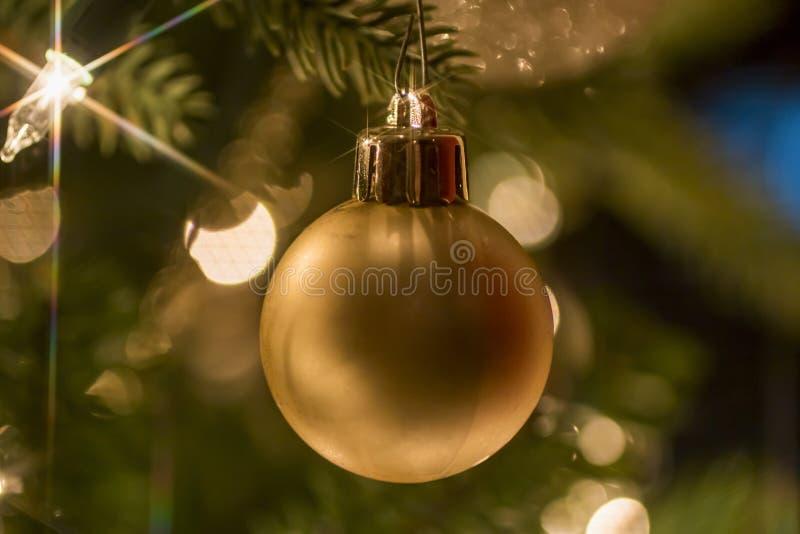 Ornamento do Natal do ouro que pendura na árvore fotografia de stock