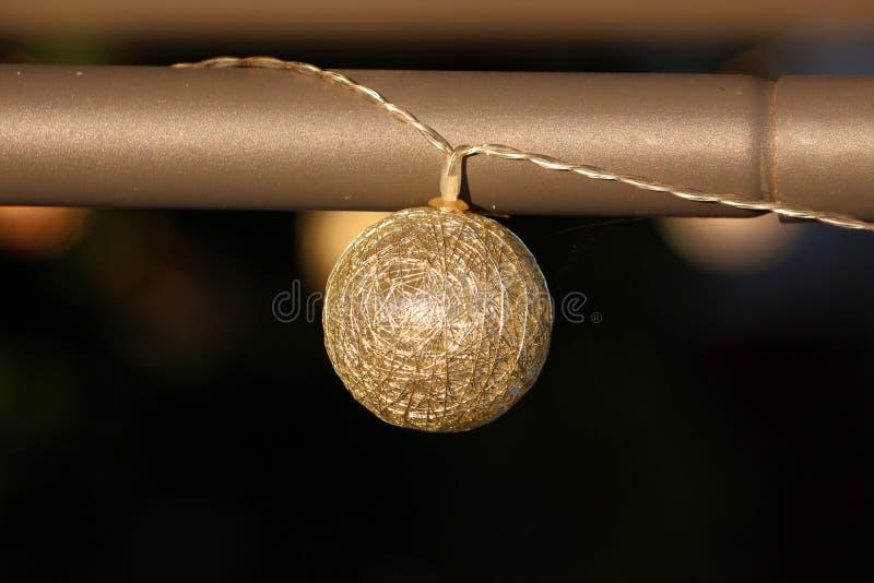 Ornamento dorato della palla di natale del cavo con la luce interna del LED appesa dal ricevimento all'aperto aspettante del palo immagine stock
