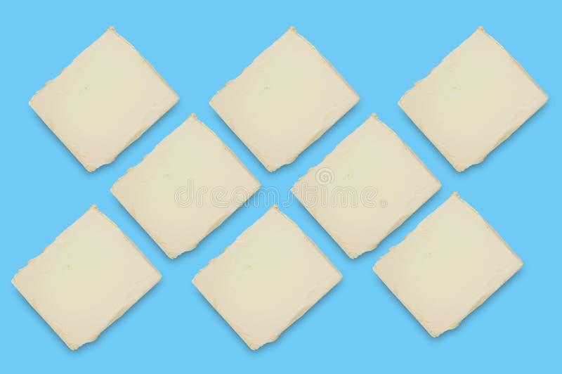 Ornamento dos tijolos da manteiga ou da margarina gorda no centro da tabela azul na cozinha Vista superior imagem de stock royalty free