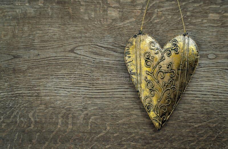 Ornamento dourado rústico do coração no fundo de madeira do vintage fotos de stock