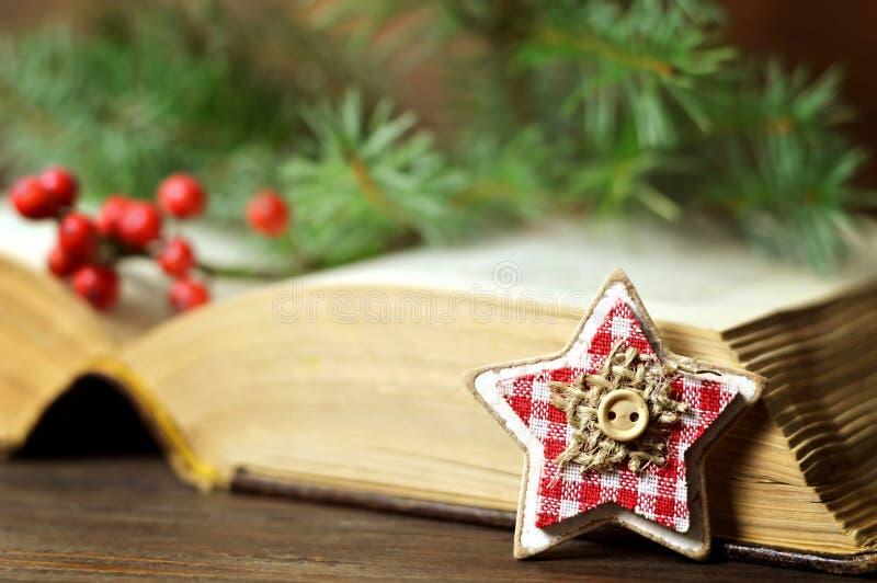 ornamento Estrela-dado forma, bagas do Natal e um livro velho imagem de stock