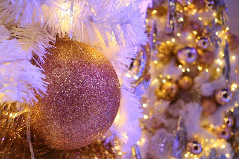 ornamento a forma di palla di Natale di scintillio dell'Rosa-oro con l'albero di Natale scintillante vago nel fondo immagini stock libere da diritti