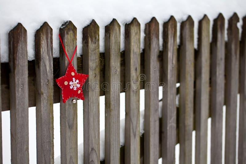 Ornamento rojo de la estrella de la Navidad blanca en la cerca vieja fotografía de archivo
