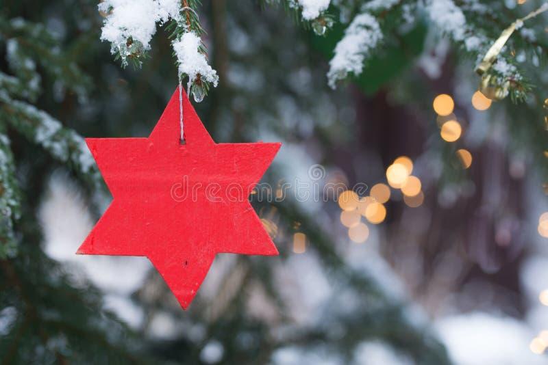 Ornamento rojo de la Navidad de la estrella haning en un árbol de abeto con nieve y luces imagenes de archivo