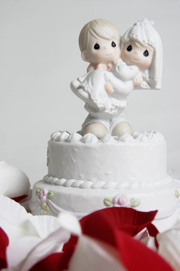 Ornamento sveglio della sposa di trasporto dello sposo in cima alla torta di cerimonia nuziale immagine stock libera da diritti
