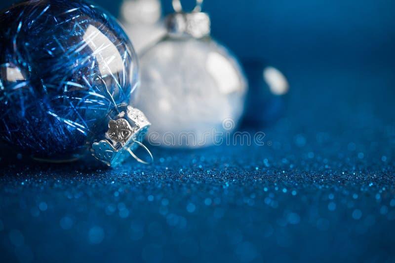 Ornamentos blancos y azules de la Navidad en fondo azul marino del brillo con el espacio para el texto Tarjeta de la Feliz Navida foto de archivo