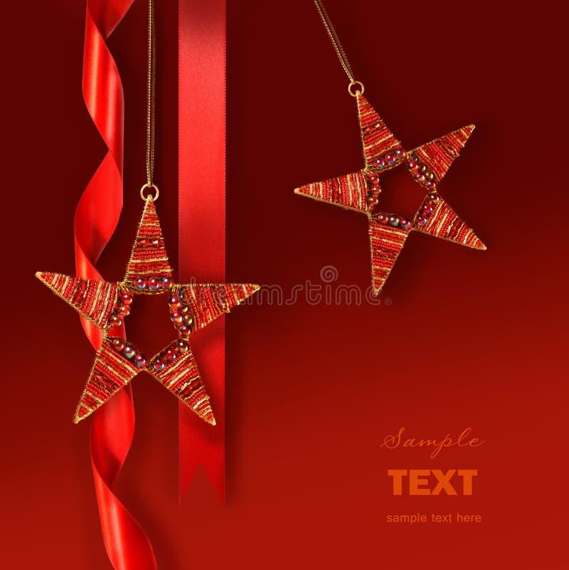 Ornamentos de la estrella de la Navidad contra fondo rojo fotos de archivo