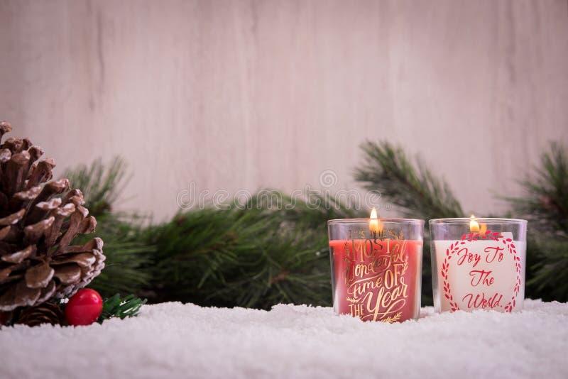 Ornamentos de la Navidad con nieve, el árbol de pino, la vela roja y las luces de Navidad fotografía de archivo