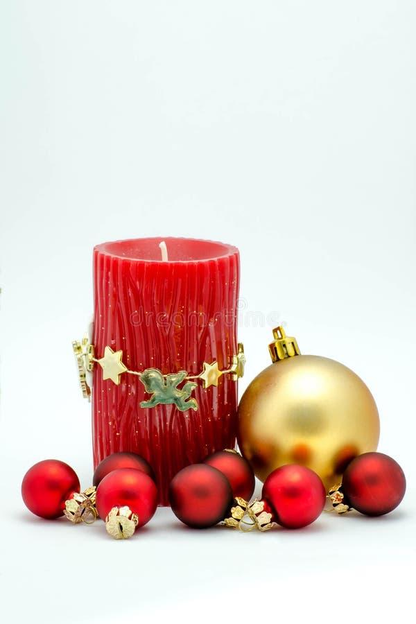 Ornamentos de la Navidad - vela y rojo y ornamentos rojos del oro imagenes de archivo