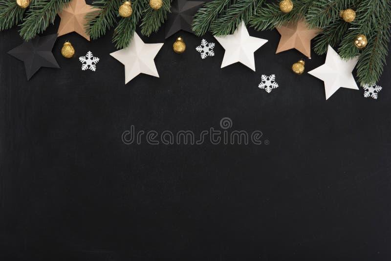 Ornamentos de las estrellas y de la Navidad, diseño de la frontera, en tablero trasero fotos de archivo libres de regalías