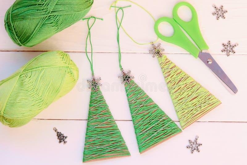 Ornamentos de los árboles de navidad en un fondo de madera Ornamentos simples de los árboles de navidad hechos de la caja de cart imágenes de archivo libres de regalías