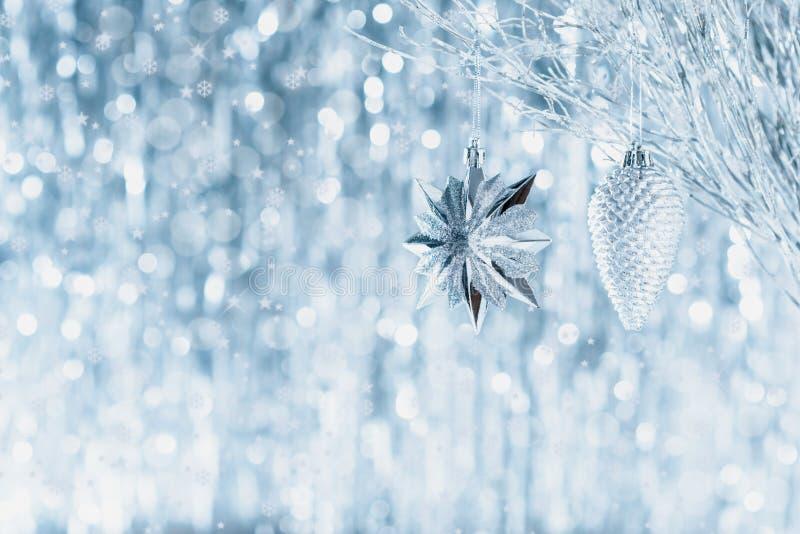 Ornamentos de plata brillantes de la Navidad que cuelgan en un árbol, con las luces de la Navidad defocused en el fondo La Navida fotos de archivo libres de regalías