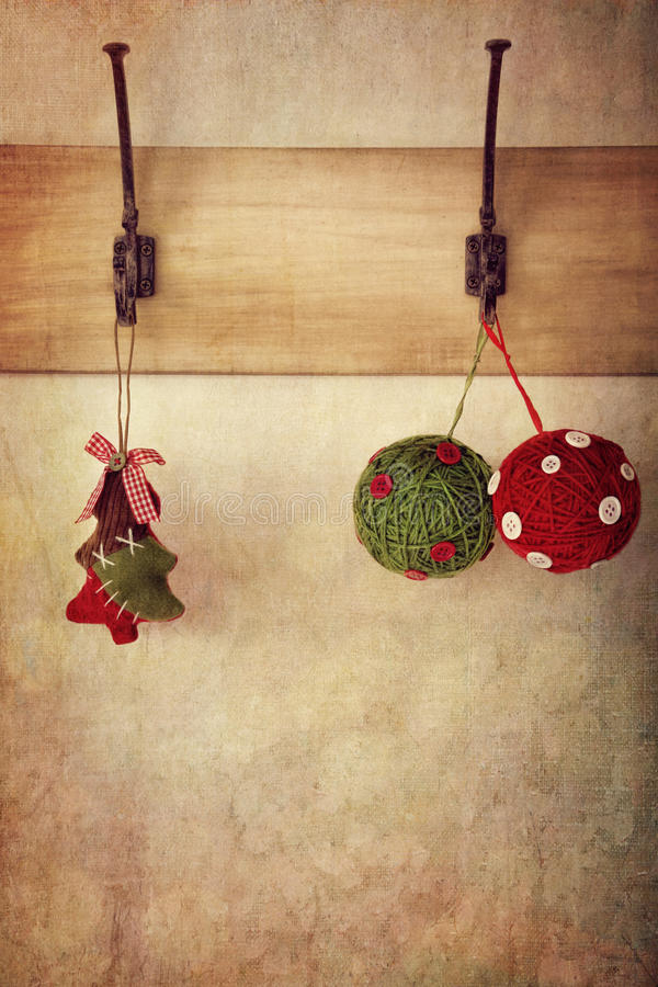 Ornamentos del día de fiesta que cuelgan en los ganchos de leva antiguos de la pared fotos de archivo