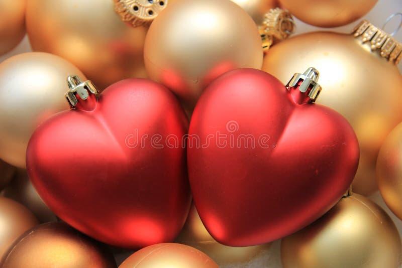 Ornamentos en forma de corazón rojos de la Navidad imagen de archivo