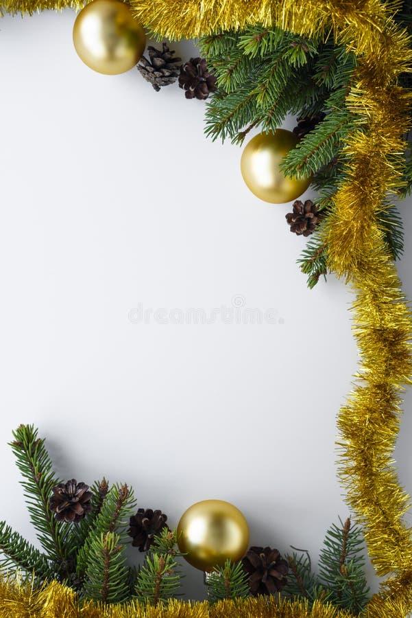 Ornamentos festivos como marco de la Navidad con el espacio de la copia Ramas de árbol de la picea, conos, chucherías del oro y m fotografía de archivo libre de regalías