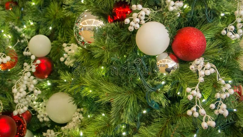 Ornamentos mezclados de la Navidad del primer en árbol con las luces borrosas en marco fotografía de archivo libre de regalías