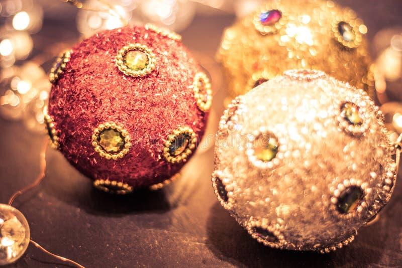 Ornamentos redondos cubiertos en joyas ricas y brillo, chucherías y luces suaves para el día de fiesta de la Navidad, tono partid imágenes de archivo libres de regalías