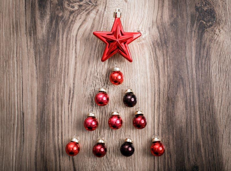 Ornamentos rojos de la Navidad bajo la forma de árbol de Navidad en un fondo de madera rústico Tarjeta de la Feliz Navidad Feliz  fotos de archivo libres de regalías