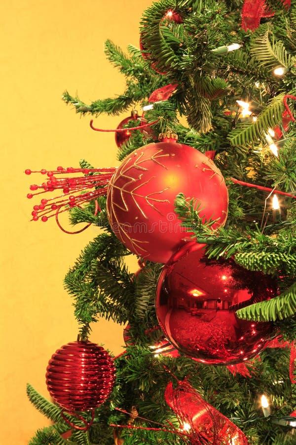 Ornamentos rojos de la Navidad en el árbol de navidad del Lit fotografía de archivo