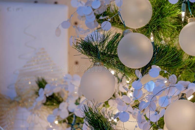 Ornamentos y luces en un árbol de navidad del día de fiesta fotografía de archivo libre de regalías