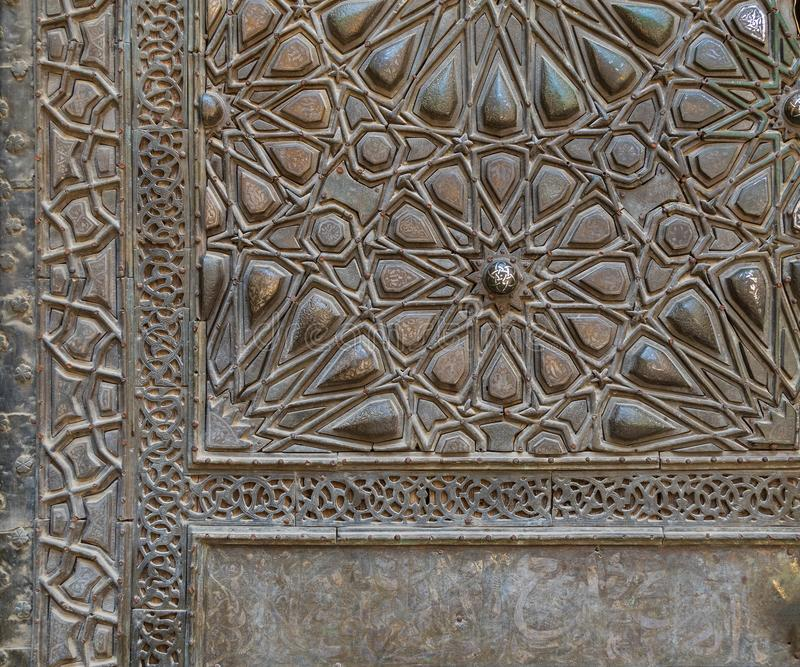 Ornaments of the bronze plate door of ancient historic mosque of Sultan Basque, Cairo, Egypt. Ornaments of the bronze-plate ornate door of Sultan Barquq mosque stock photography