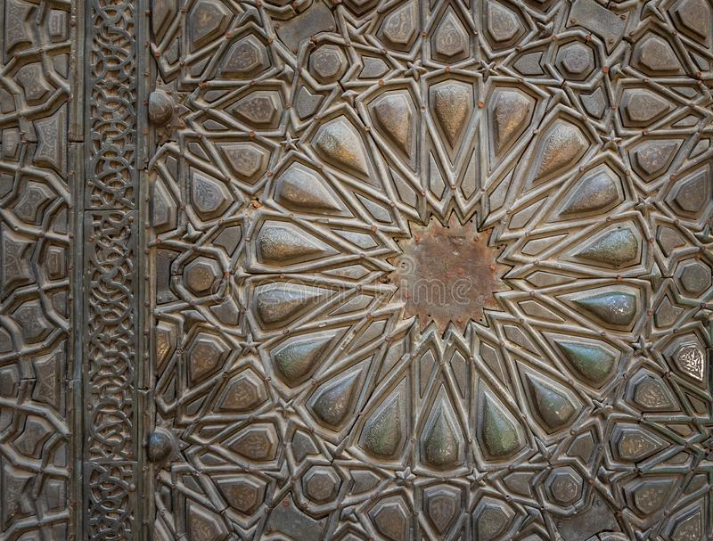 Ornaments of the bronze plate door of ancient historic mosque of Sultan Basque, Cairo, Egypt. Ornaments of the bronze-plate ornate door of Sultan Barquq mosque stock images
