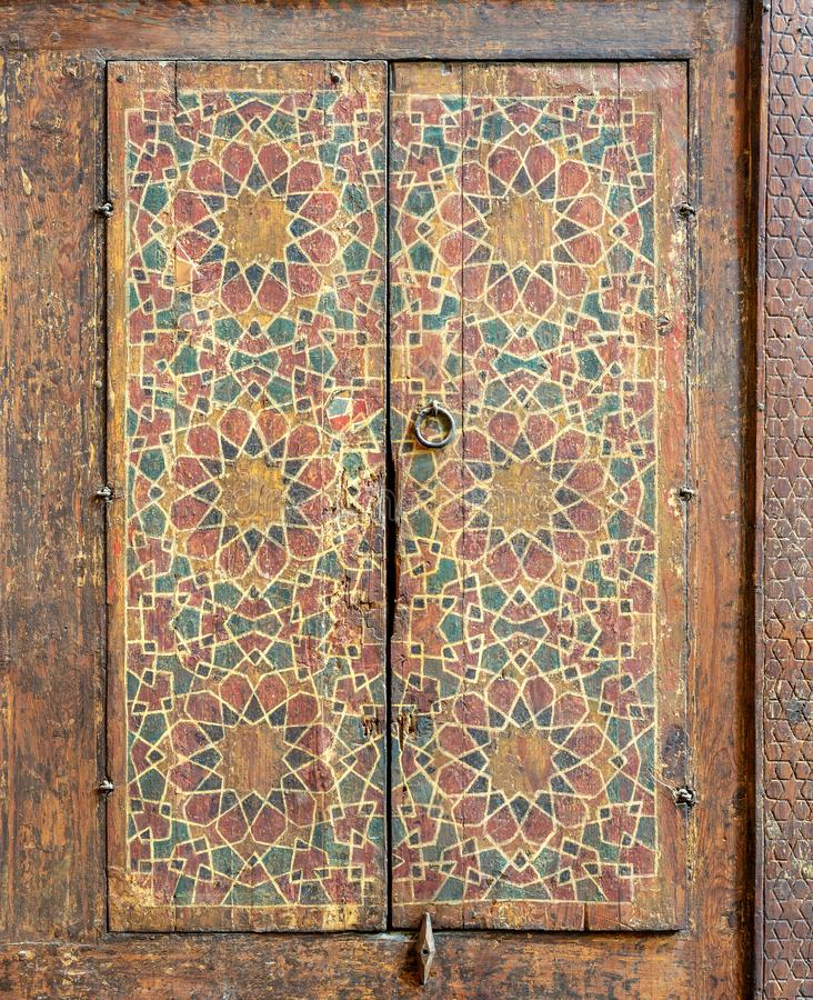 Ornaments of a wooden cupboard painted with colored geometrical patterns embedded in the walls of Sultan al Ghuri Mausoleum royalty free stock photos