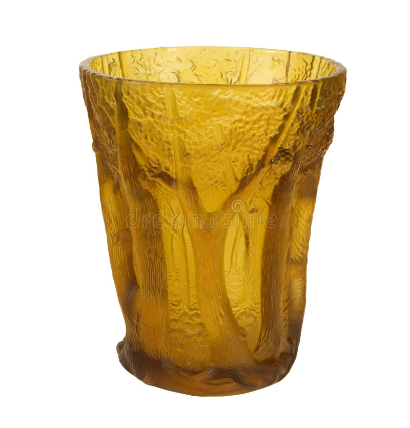 Ornate amber glass vase. Artistic amber glass vase with tree trunk design on a white background stock image