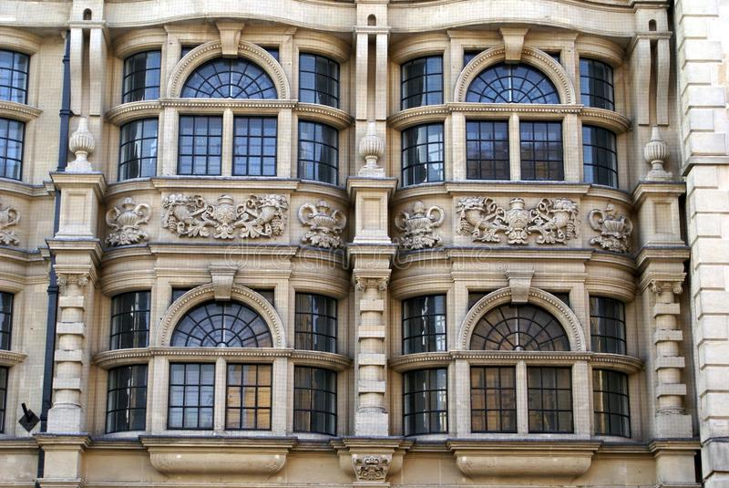 Ornate arched bay windows with sculptures & columns. Decorative facade or exterior with arched bay windows , sculptures, and columns or pillars stock image