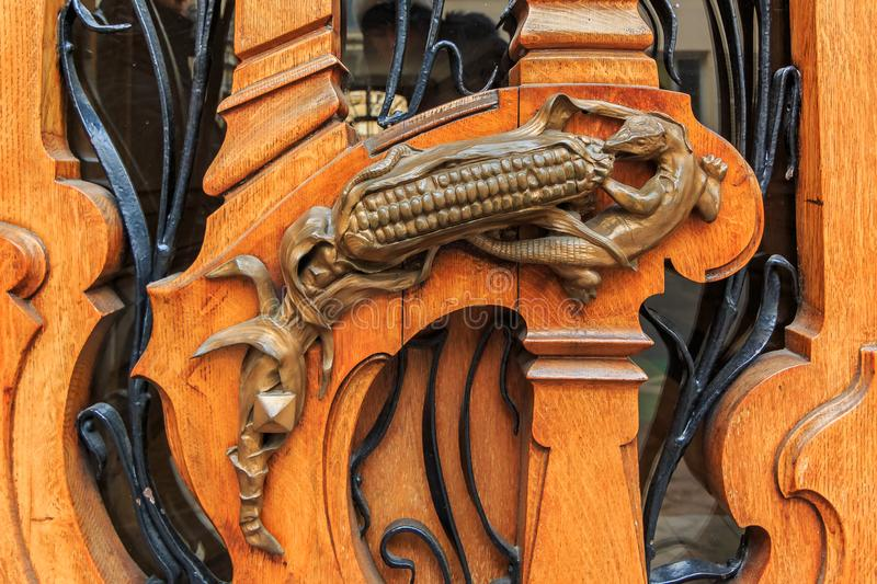 Ornate art nouveau wooden door detail with organic motif and handle shaped like a lizard eating an ear of corn in Paris, France stock photos
