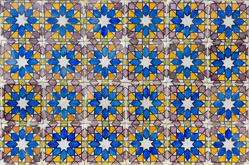 Ornate brightly colored Portugese tile texture in blue, purple, olive and yellow. Geometrical star patterned portugese tiles texture abstract antique art stock images
