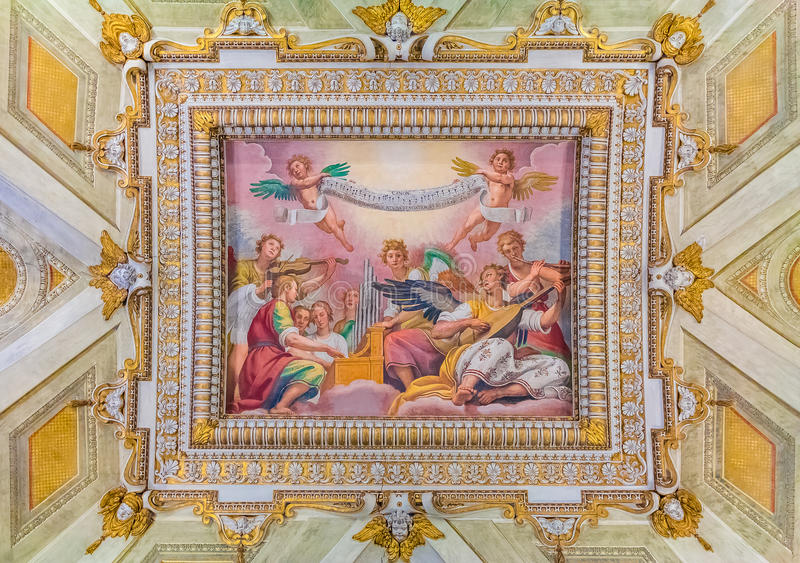 Ornate ceiling frescoes in a basilica in Rome. Rome, Italy - October 11, 2016: Detail of an antique baroque ceiling decorations of frescoes at the Basilica stock image