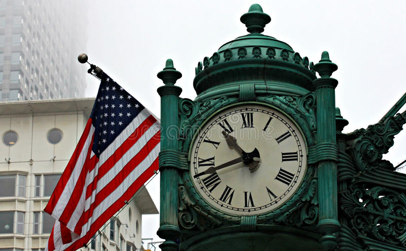 Ornate Clock and American Flag. Large clock and American flag in foggy Downtown Chicago, Illinois royalty free stock photography