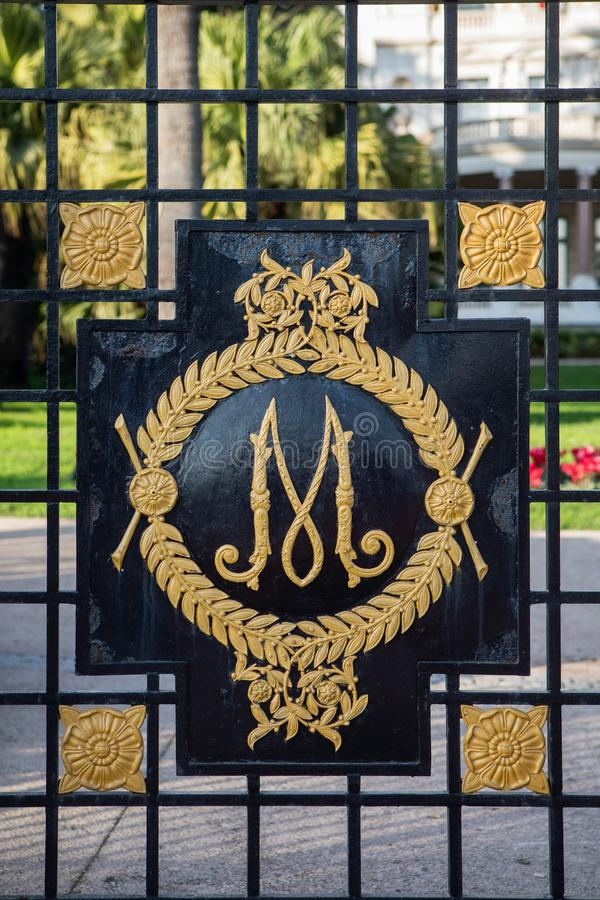 Letter M on the fence. Ornate decoration of fence with artistic monogram, letter M stock photos