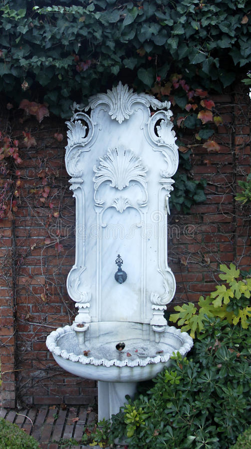 Ornate, embossed marble fountain. Old, ornate, embossed marble, ottoman fountain in the forest surrounded with plants stock photos