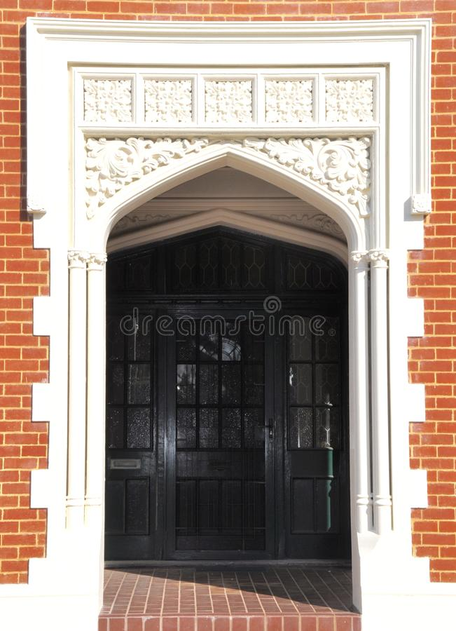 Ornate Entry Architecture and Breezeway. Ornate white entryway framing a brick exterior of a doorway with a breezeway and an inner door in view stock photos